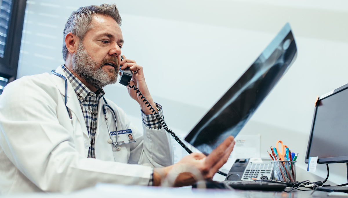 doctor-checking-x-ray-and-talking-on-telephone-at-clinic_soc