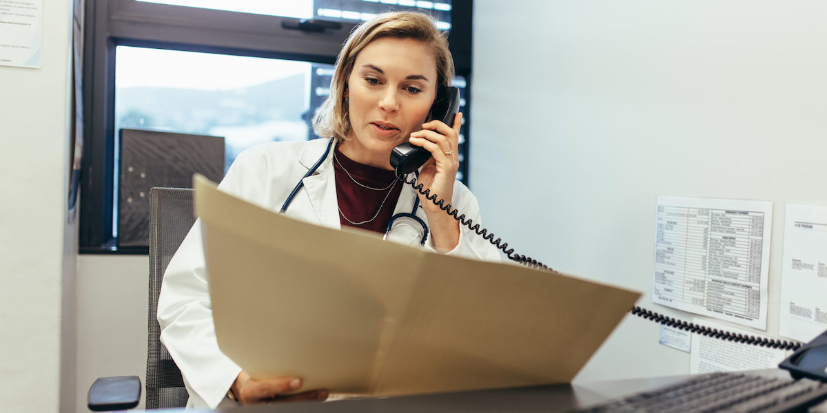 physician-on-phone-examining-medical-reports_soc